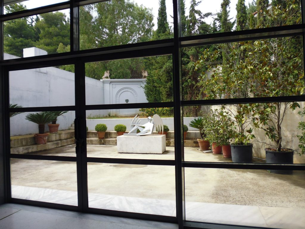 Inside the exhibition space looking out to the gardens at Vorres Museum