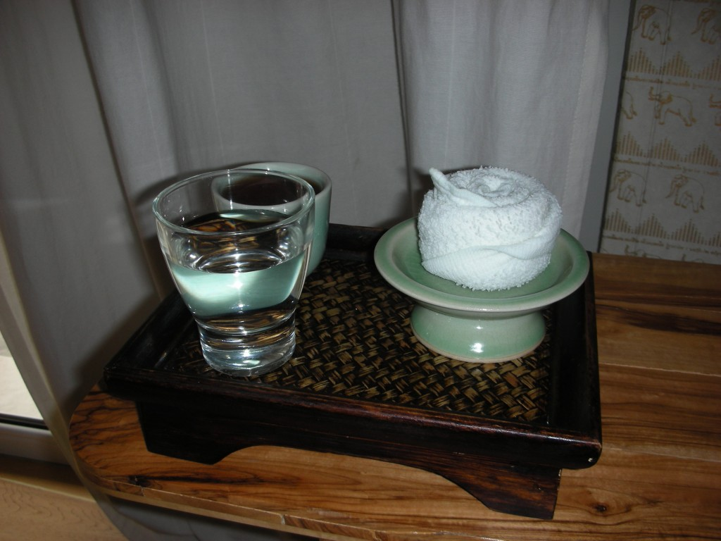Welcoming green tea and warm face cloth
