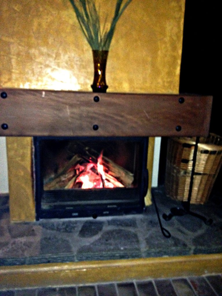 Log fire at the foot of your bed at Montanema Handmade Village